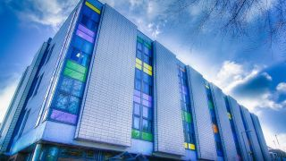 An image of the Oxford Heart Centre taken by the bus stop on the south-western slope on the John Radcliffe Hospital site. The mosaic of colourful glass panes below the windows contrast sharply against the the skyline and the main hospital building.
