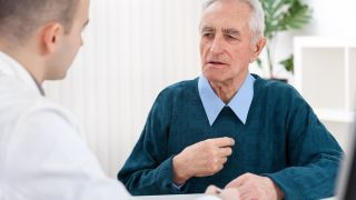 Old man in clinic setting pointing to heart