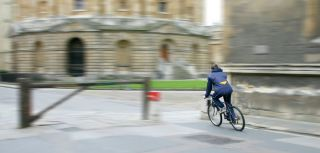 Student cycling outside Oxford University