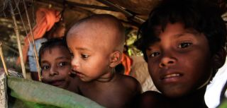 An infant IDP with his two siblings in Palinpyin village, near the coastal city of Sittwe in Rakhine state