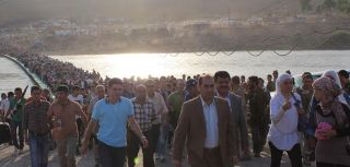 Thousands of Syrians streamed across a bridge over the Tigris River, entering Iraq