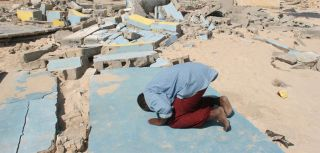 A villager prays on the remains of the mosque, Somalia