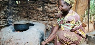 A Congolese refugee uses her mud stove and biomass briquettes to cook a meal in Nakivale refugee settlement, Uganda