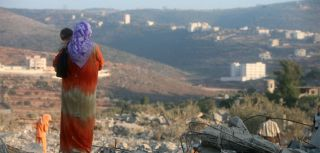 Members of a Lebanese family look out over the rubble of their home in Ayta ash-Shab
