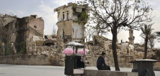 A vendor sells pink candy floss amid the ruins near the Aleppo citadel, Syria, November 2017. © UNHCR/Susan Schulman