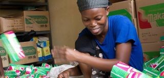A young Ugandan woman stamps expiration dates on the bottom of hand-packaged MakaPad packets