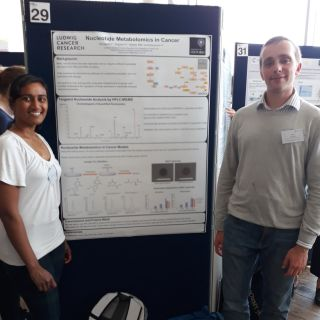 Two members of Skirmantas Kriaucionis' lab standing in front of their research poster