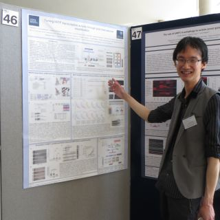 A photo of Pakavarin Louphrasitthiphol presenting his research poster