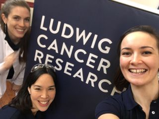 Tammie Bishop, Olivia Lombardi and Virginia Schmid posing with smiling faces next to the Ludwig Cancer Research banner