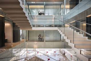 A view of the central staircase in the atrium showing the new video meeting pods