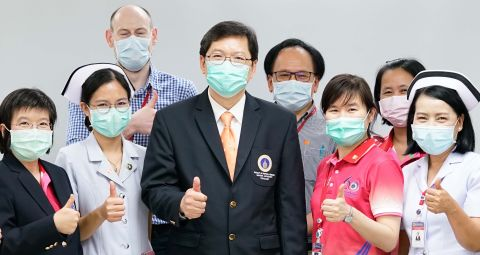Thai healthcare staff wearing masks and doing thumbs up
