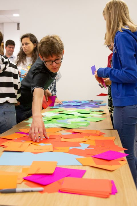 A project participant is reaching to look at a colourful piece of card from amongst a long table of reds greens oranges - cards that reflect thoughts and feelings of participants