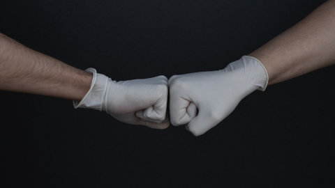 Fist bump wearing surgical gloves