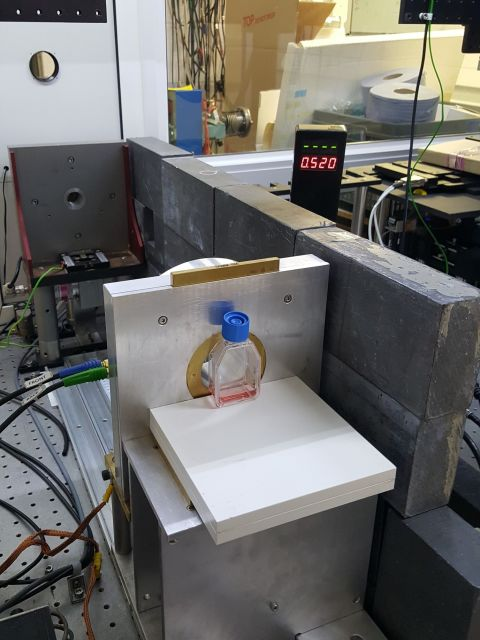 Figure 1: One of the setups used for irradiating cells with FLASH irradiation, using our dedicated linear accelerator. The radiation beam comes out of the circular opening in the upper left corner. The beam spreads out as it travels towards the flask and is collimated (shaped) by the brass plate in the aluminium casing with a circular aperture, just prior to hitting the flask containing our monolayer of cells (attached to the inside surface of the flask closest to the brass collimator).