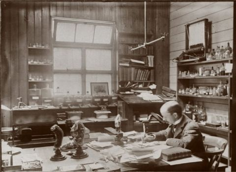Arthur Thomson writing at desk in a room filled with papers, microscopes and bottles of chemicals