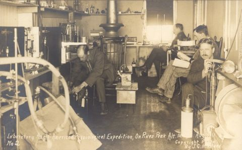 Several men working with various lab equipment