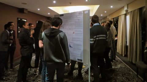 A photo of the poster session at the Ludwig retreat showing scientific posters on boards and people presenting, discussing and reading the posters.