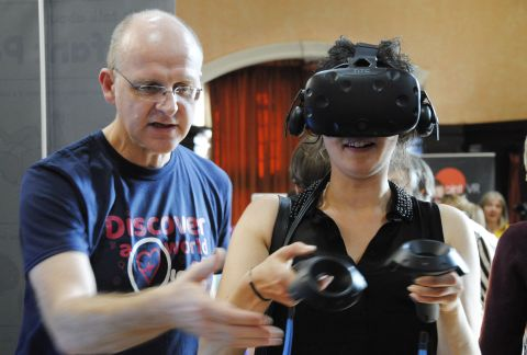 Steve Taylor leads a visitor on a VR experience at a science festival