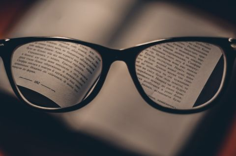 Reading glasses hovering over an open book.