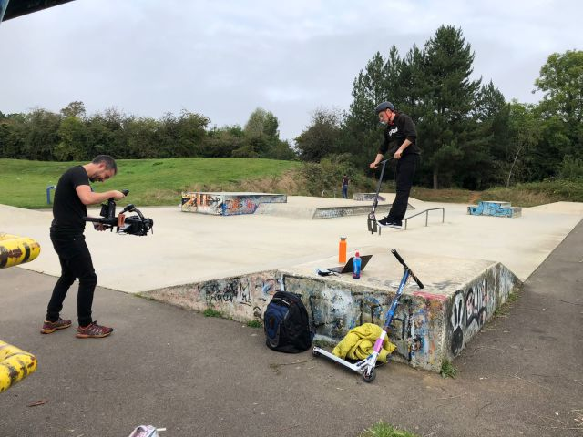 Someone on a stunt scooter is in the air, on a skate park. They are being filmed by someone.