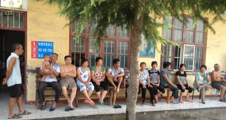 Queue of people sitting outside a clinic in China