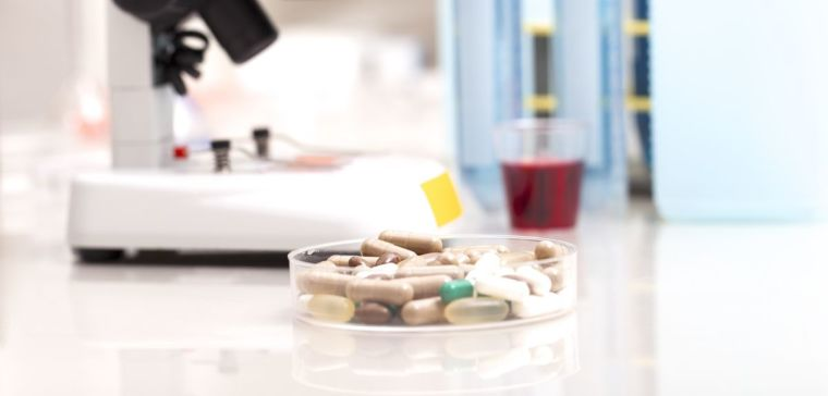 A petri dish filled with different types of medicinal pills in a lab