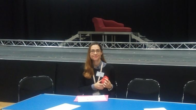 Dr Sophia Malandraki-Miller sat at a table holding a prosthetic heart in front of a stage at Oxford High School