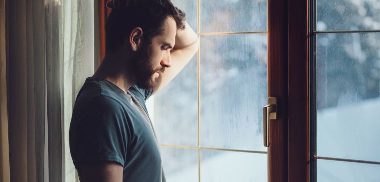 Young sad man standing by the window