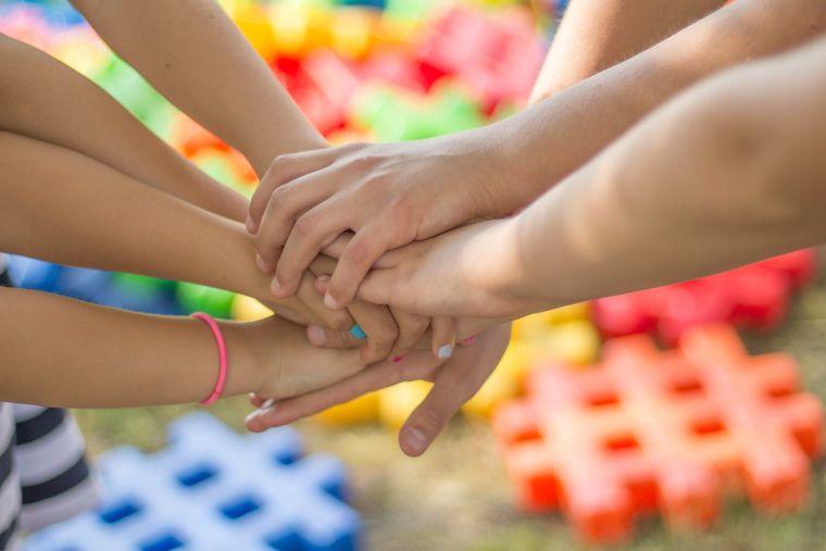 Children put hands together.