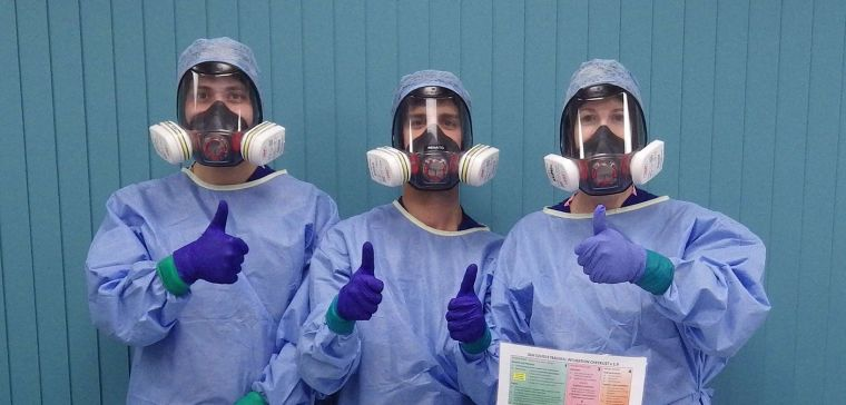 Intubation team of two men and a woman in full personal protective equipment