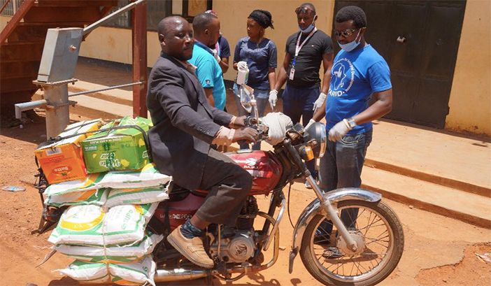 Photo of members of the refugee-led organisation YARID delivering food and other items by motorbike to refugees in Kampala.
