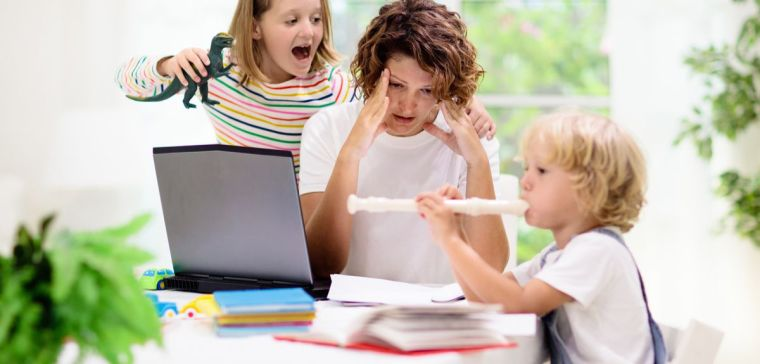Mother working from home with kids. Quarantine and closed school during coronavirus outbreak. Children make noise and disturb woman at work.