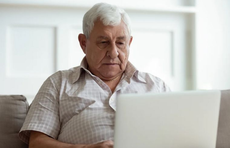 Serious older man using laptop close up, looking at the screen