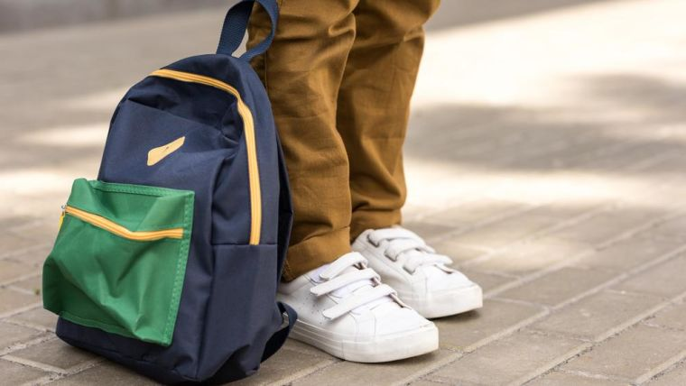 A young person's legs, shoes and school bag