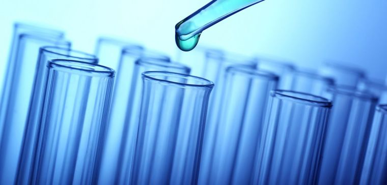 Closeup of a pipette dropping a green sample into a test tube on light blue background