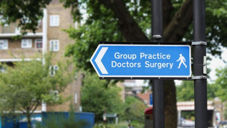 Photo of a street signpost pointing left, reading 'Group Practice Doctors' Surgery'