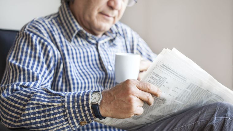 A man reads a paper while drinking a hot drink.