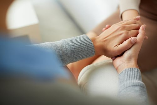 Two people holding hands across the table.