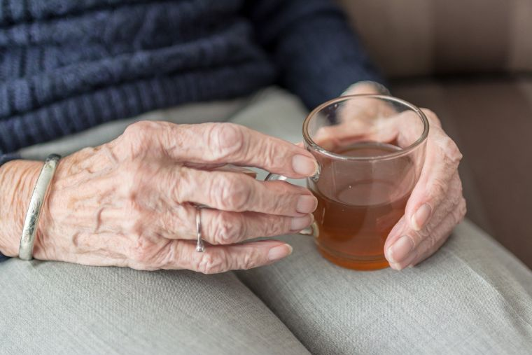 Older hands clasping a hot drink.