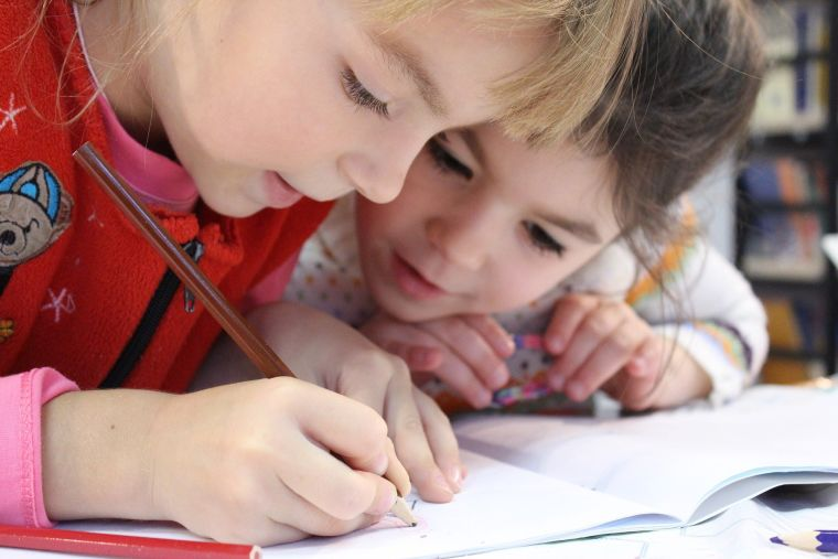 Two girls are leaning over a notebook, one is drawing.