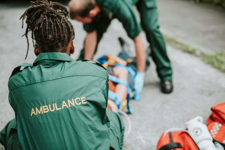 2 paramedics lifting a stretcher