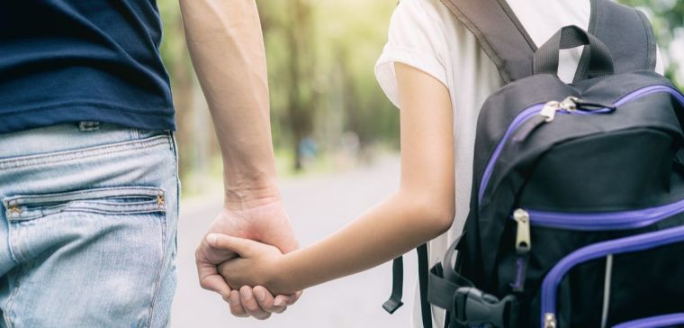 Father's holds daughter's hand in a park go to school.