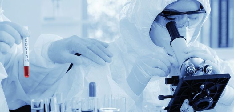 Scientist in biohazard protection clothing analysing sample with a microscope with another scientist holding coronavirus covid-19 blood sample tube on hand in a laboratory
