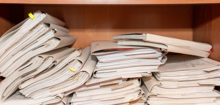 Paper documents stacked in an archive shelf