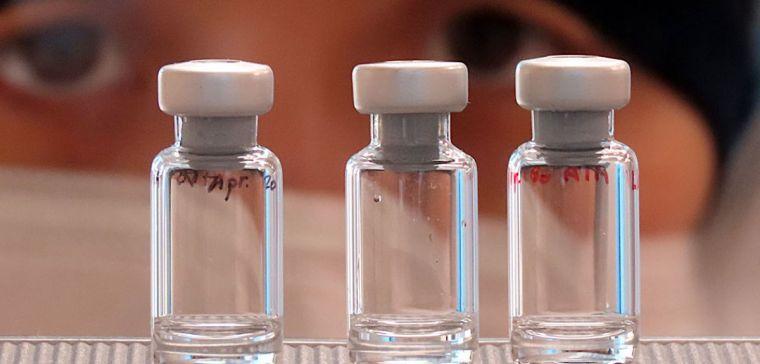 Scientist looking at three vaccine vials