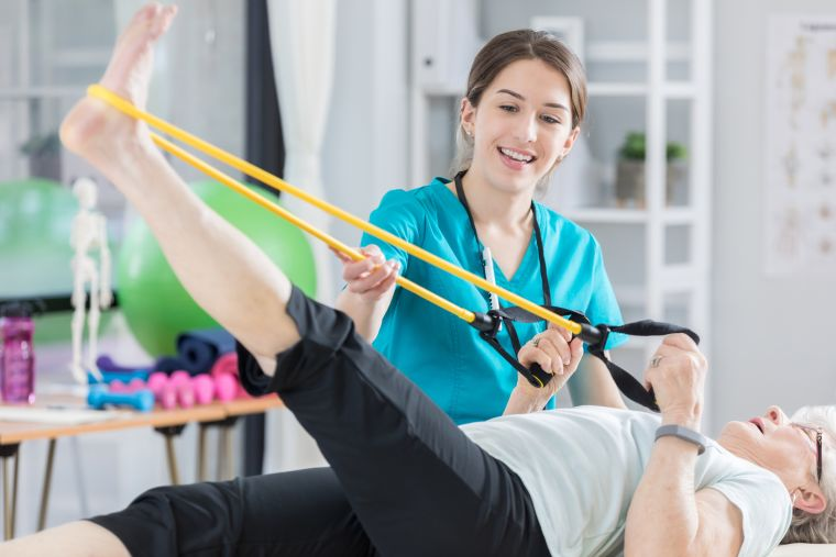 Patient stretching leg with resistant bands while therapist looks on
