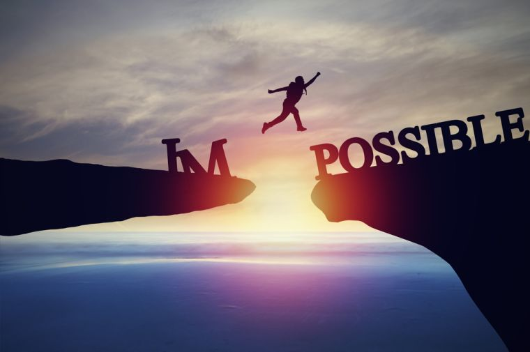 Image shows someone jumping between rocks with the broken word on each side saying 'impossible'.