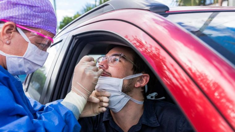 Photo of a man receiving a drive through COVID-19 swab test.