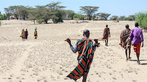Pastoralist Turkana people walking across dry, hot land
