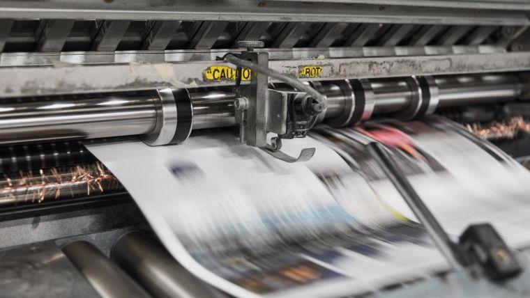 Newspaper rushing through a printing press